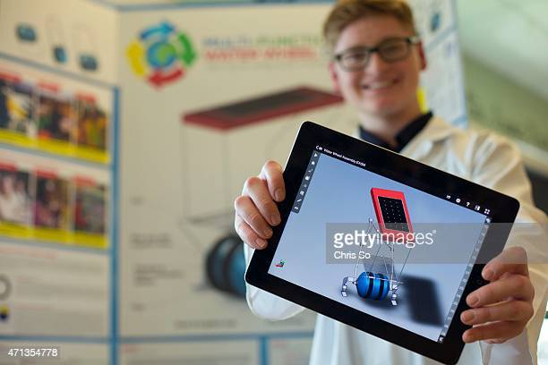 St Brother Andre Catholic High School Grade 10 student Aidan Aird holds up a 3D auto CAD rendering of a 'MultiFuntional Water Wheel Cart ' a device...