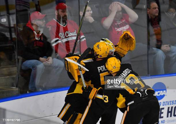 St Cloud State Huskies fans react as Zackarias Skog Ryan Polin and Hugo Reinhardt of the American International Yellow Jackets celebrate after the...