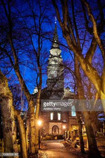St Cuthbert's Churchyard with twisted bare winter trees at night, Edinburgh