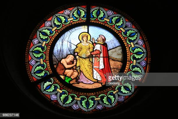 St. Elizabeth of Hungary, who is going to do charity to the poor, surprised on a path by her husband, the Prince of Thuringia. Stained glass. Church...