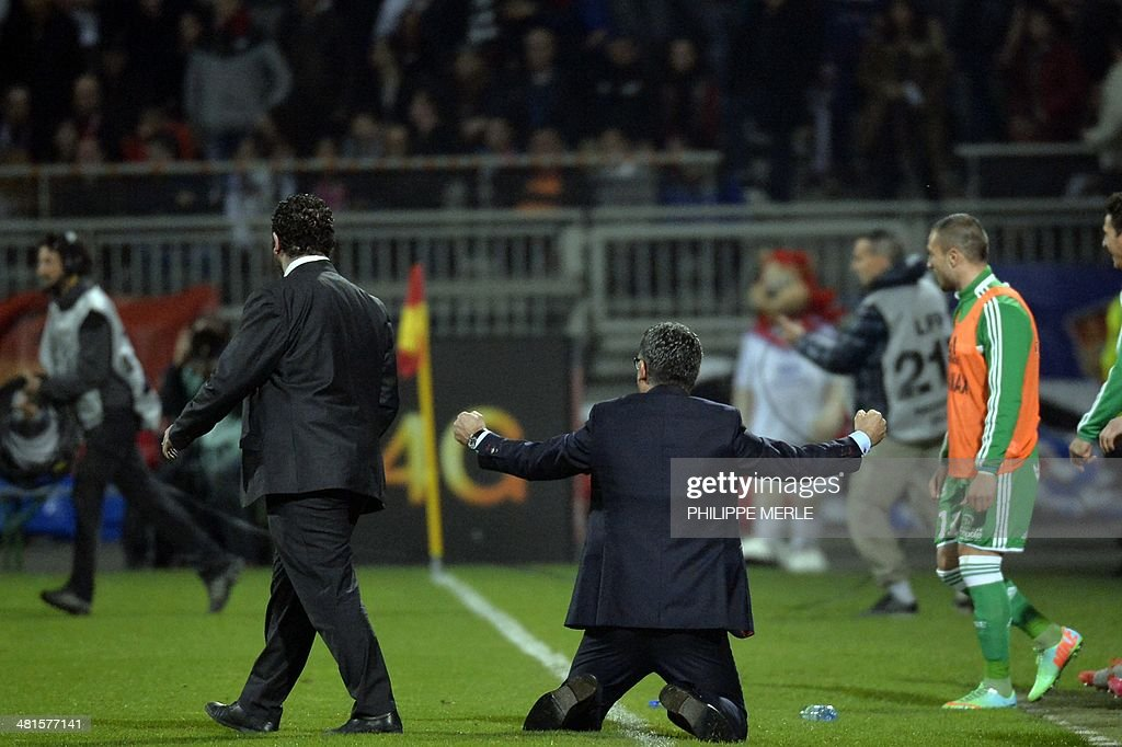 St Etienne's French coach Christophe Galtier (C) kneels onto the pitch as he reacts after Saint Etienne defeated Lyon 2-1 in their French L1 football match Olympique Lyonnais (OL) vs Saint-Etienne (ASSE) at the Gerland stadium in Lyon, southeastern France, on March 30, 2014.
