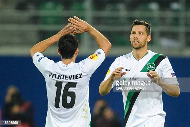 St Gallen's French defender Stephane Besle is congratulated by St Gallen's Swiss midfielder Matias Vitkieviez during the UEFA Europa League Group A...