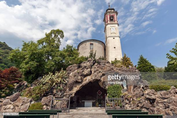 st. georg parish church, below a replica of the grotto of lourdes, mariengrotte, cannero riviera, lago maggiore, verbano-cusio-ossola province, piedmont region, italy - province of verbano cusio ossola stock pictures, royalty-free photos & images