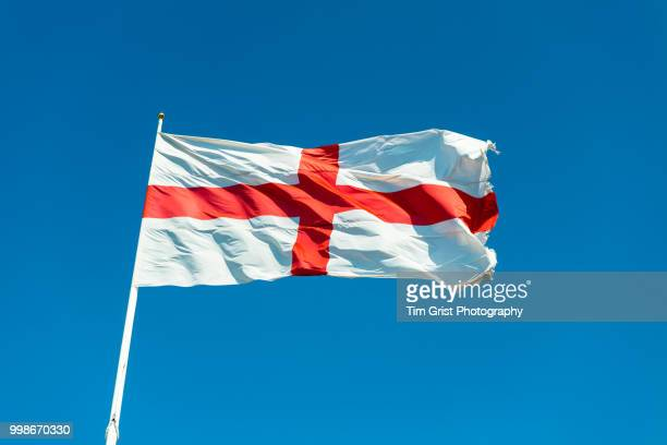 st george cross flag of england against a blue sky - bandiera inglese foto e immagini stock