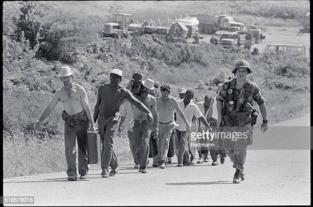 Cuban prisoners under guard of a US Army soldier carry drinking water up a hill near their prison compound at the Point Salines Airport The United...