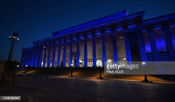 St Georges Hall and St John's Beacon is lit up by blue lights in Liverpool, north-west England on March 26 as a sign of admiration for the National...