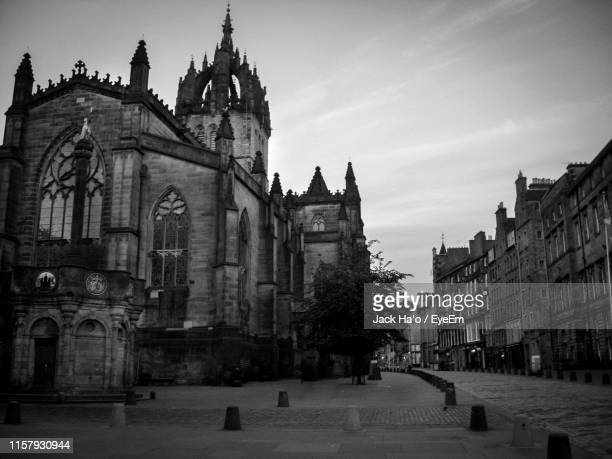 st giles cathedral by buildings in city against sky - st. giles cathedral stock pictures, royalty-free photos & images