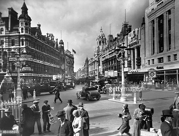 St Giles Circus City of Westminster London A man is standing on the corner selling newspapers He is holding a poster possibly with the newspaper...