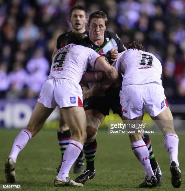 St Helens' James Roby and Josh Perry tackle Harlequins' Oliver Wilkes during the engage Super League match at the Stobart Stadium Halton