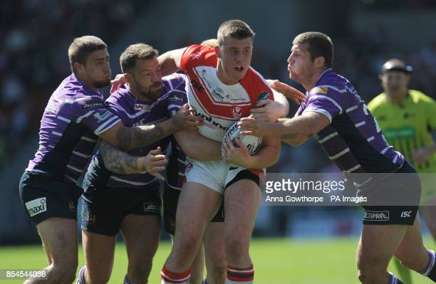St Helens' Joe Greenwood is held be a strong Wigan Warriors' defence during the First Utility Super League match at Langtree Park St Helens