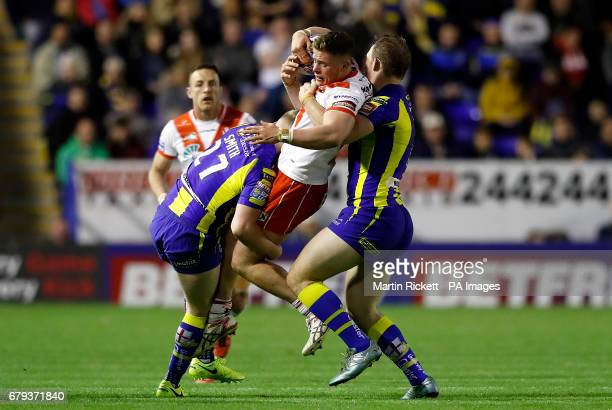 St Helens' Morgan Knowles is tackled by Warrington Wolves' Morgan Smith and George King , during the Betfred Super League match at the Halliwell...