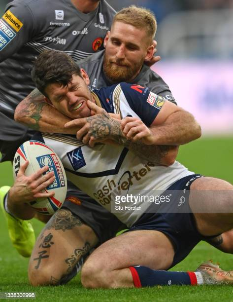 St Helens player Lachlan Coote is tackled by Sam Tomkins of the Dragons during the Betfred Super League match between St Helens and Catalans Dragons...