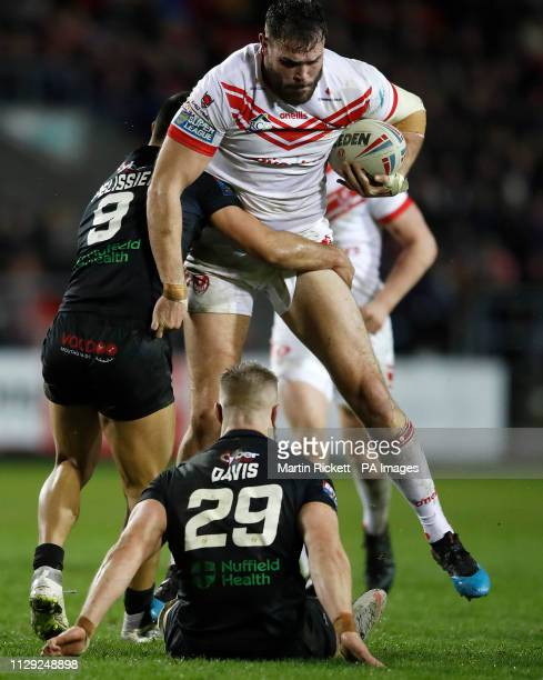 St Helens Saints' Alex Walmsley is tackled by London Broncos' Eloi Pelissier and Matthew Davies during the Betfred Super League match at the Totally...
