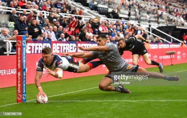 St Helens wing Tommy Makinson dives on the corner to score the first Sainst try despite the attentions of Dragons player Fouad Yaha during the...