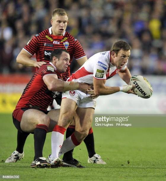 St Helens's James Roby off loads the ball as he is tackled by Warrington Wolves's Adrian Morley during the Stobart Super League Semi Final Langtree...