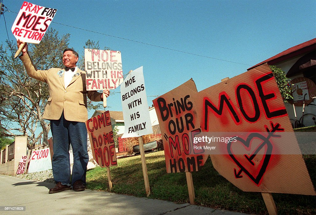 St  James Davis holds signs outside his West Covina home  He
