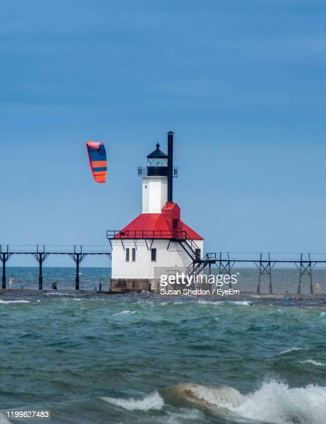 st joe michigan, usa , september 14 2019 kite boarder surfs near the light house landmark - great lakes stock pictures, royalty-free photos & images