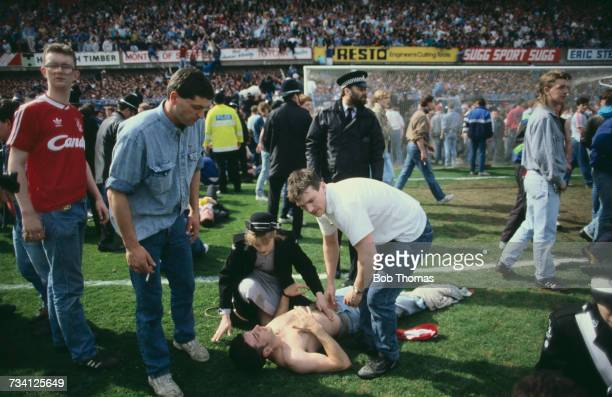 A St John Ambulance volunteer attends to a casualty on the pitch at Hillsborough football stadium in Sheffield after a human crush at an FA Cup...