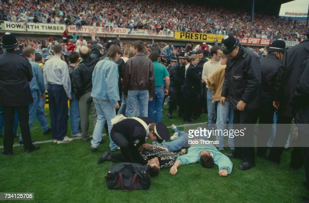 A St John Ambulance volunteer attends to casualties on the pitch at Hillsborough football stadium in Sheffield after a human crush at an FA Cup...