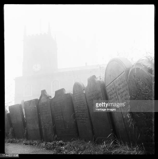 St John the Baptist's Church King Street Longton StokeonTrent 19651968 Gravestones lining a pathway in the churchyard of the church which is visible...