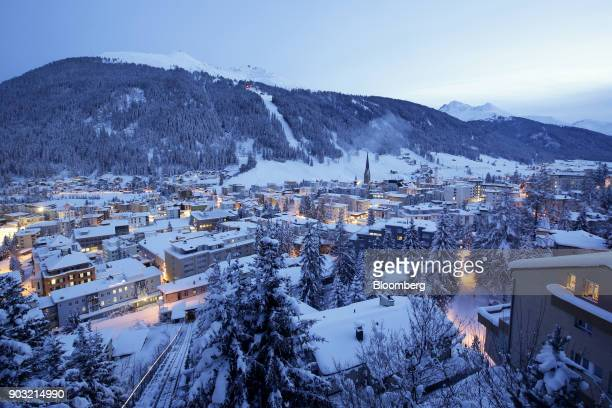 St John's church centre right sits surrounded by snowcovered residential buildings as night falls in Davos Switzerland on Monday Jan 18 2015...