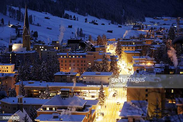 St John's church left sits surrounded by snowcovered residential buildings as illuminations light the main street at night in Davos Switzerland on...