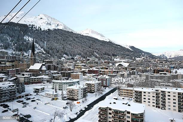St John's church left stands surrounded by snowcovered residential and commercial buildings seen from the Jakobshorn cable car as it travels up the...