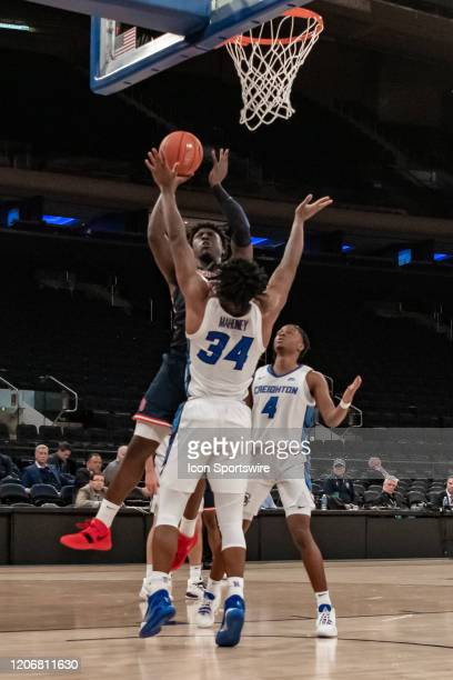 St John's Red Storm forward Marcellus Earlington shoots over Creighton Bluejays guard Denzel Mahoney during the first half of the Big East tournament...