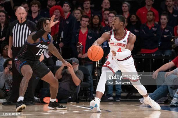St John's Red Storm Guard Greg Williams Jr passes the ball with DePaul Blue Demons Forward Darious Hall defending during the first half of the...
