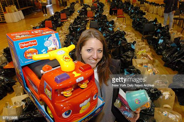 St. John's University student Jennifer Lebowitz holds up a toy fire engine that will go to a lucky child during St. John's Bread and Life's 10th...