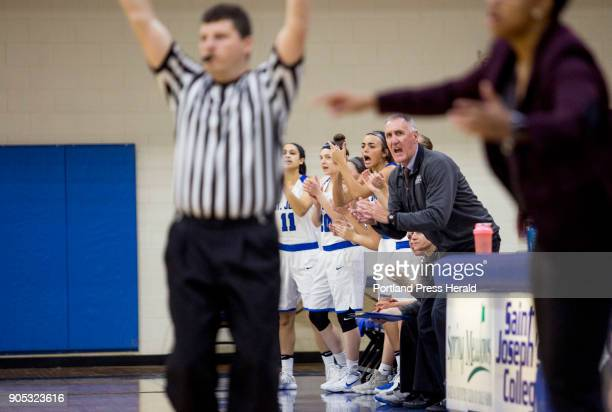 St Joseph's College player and their head coach Mike McDevitt celebrate a basket during the first half of their game against Johnson Wales University...