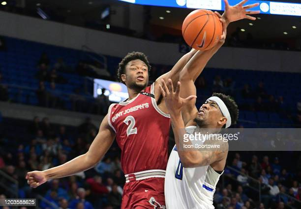 St Joseph's forward Myles Douglas tries to block a shot by Saint Louis guard Jordan Goodwin during an Atlantic 10 Conference basketball game between...