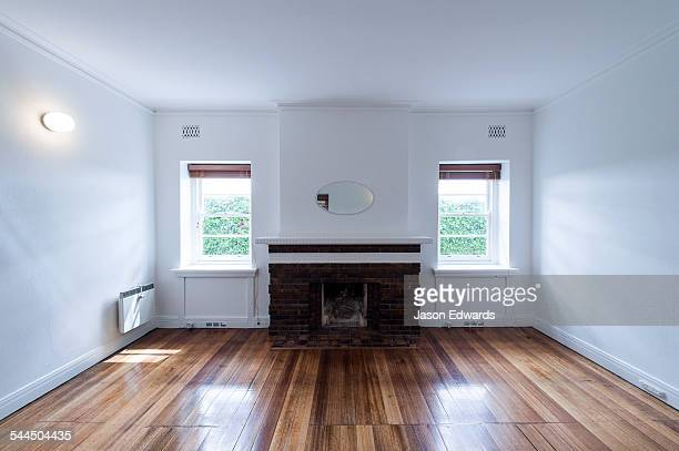 A living room and fireplace above polished floorboards in an empty rental apartment freshly painted in white.