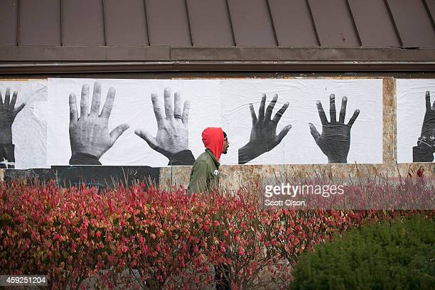 St Louis artist Damon Davis installs posters from his Push Forward Project on a boarded up business along West Florissant Street on November 19 2014...