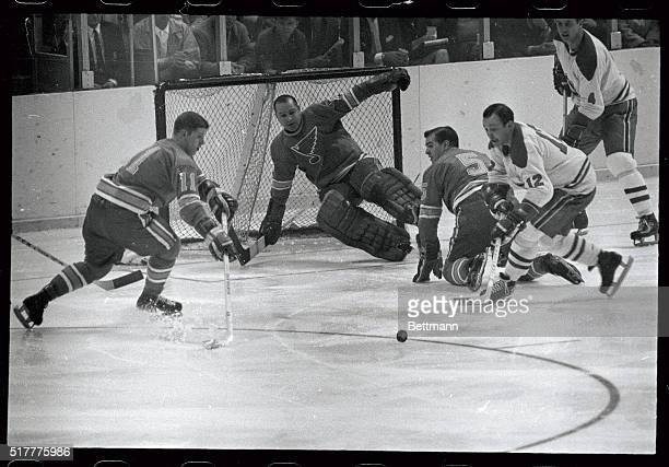 St Louis Blue's Bob Plager hits the ice as goalie Glenn Hall blocks a shot by Montreal's Yvan Cournoyer and pushes the puck in front of the goal...