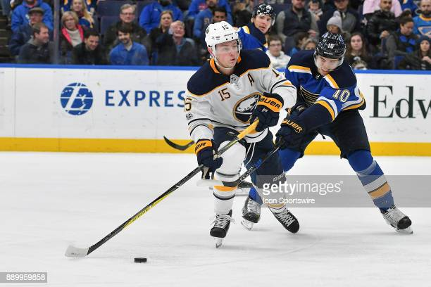 St Louis Blues center Brayden Schenn tries to knock the puck away from Buffalo Sabres center Jack Eichel as he sets up for a shot during a NHL game...