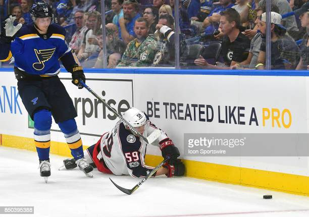 St Louis Blues center Oskar Sundqvist and Columbus Blue Jackets defenseman Ryan Collins watch a loose puck on the end boards during a preseason...
