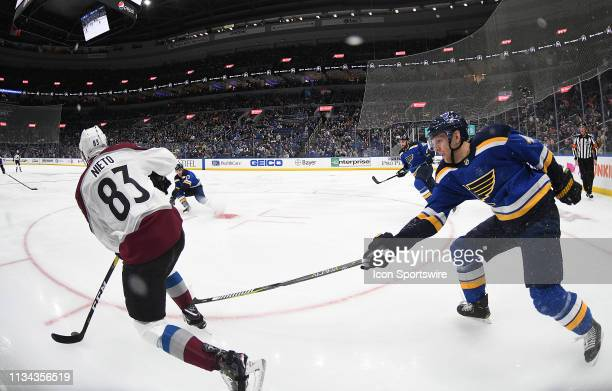 St Louis Blues defenseman Joel Edmundson reaches in to get the puck from Colorado Avalanche leftwing Matt Nielo during a NHL game between the...