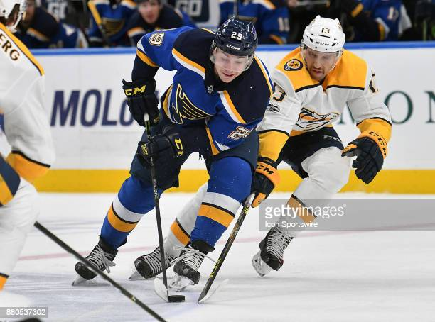St Louis Blues defenseman Vince Dunn competes for the puck with Nashville Predators center Nick Bonino during a NHL hockey game between the Nashville...