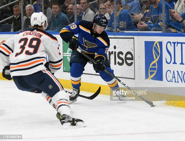 St Louis Blues defenseman Vince Dunn controls the puck with pressure from Edmonton Oilers rightwing Alex Chiasson during an NHL game between the...