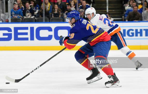 St Louis Blues defenseman Vince Dunn skates with the puck with pressure from New York Islanders center Brock Nelson during an NHL game between the...