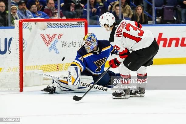 St Louis Blues goaltender Carter Hutton left makes a save on New Jersey Devils' Nico Hischier during the overtime period of an NHL hockey game...
