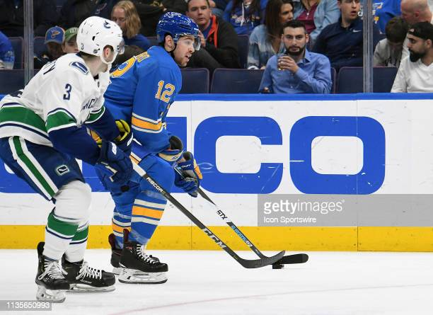St Louis Blues leftwing Zach Sanford skates with the puck ahead of Vancouver Canucks defenseman Brogan Rafferty during a NHL game between the...