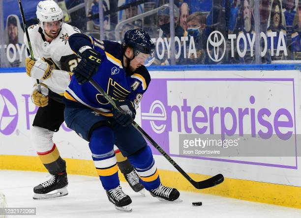 St. Louis Blues right wing Vladimir Tarasenko controls the puck as Vegas Golden Knights defenseman Shea Theodore looks on during an NHL game between...