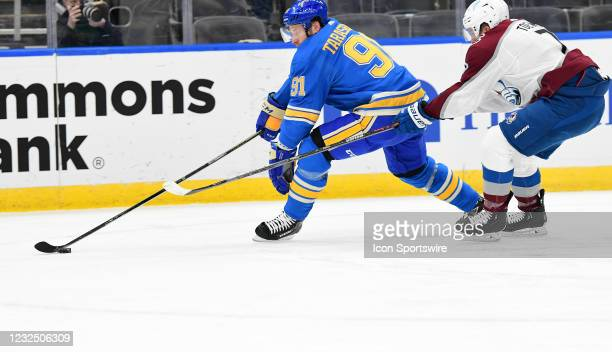 St. Louis Blues right wing Vladimir Tarasenko skates with the puck ahead of Colorado Avalanche defenseman Devon Toews during a NHL game between the...