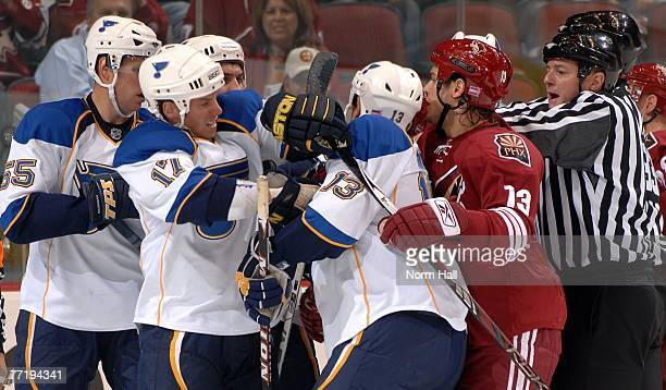 St Louis Blues right winger Dan Hinote steps between Blues center Ryan Johnson and Phoenix Coyotes forward Daniel Carcillo during the first period on...