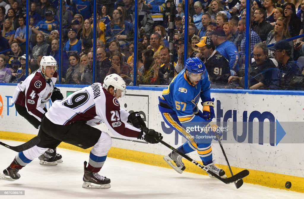 St. Louis Blues rightwing David Perron (57) skates with the puck ahead of Colorado Avalanche center Nathan MacKinnon (29) during an NHL game between the Colorado Avalanche and the St. Louis Blues on April 09, 2017, at the Scottrade Center in St. Louis, MO. The Blues won, 3-2.