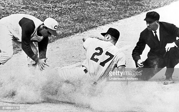 St Louis Cardinal outfielder Don Taussig stirs up a cloud of dust on an attempted steal but is called out at third by umpire Augie Donatelli as Reds...