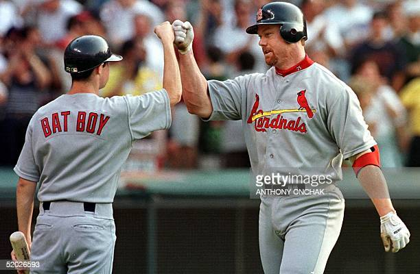 St Louis Cardinals' batter Mark McGwire is congratulated by team bat boy Willie Jenkins after he hit a solo home run over the left field wall during...