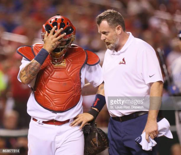 St Louis Cardinals catcher Yadier Molina is tended to by assistant athletic trainer Chris Conroy after Molina was hit in the head by a second...